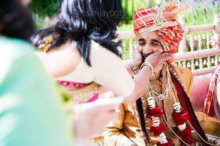 Hindu Wedding groom having his cheeks squashed