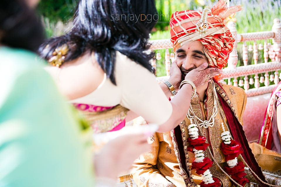 Hindu Wedding groom having his cheeks squashed