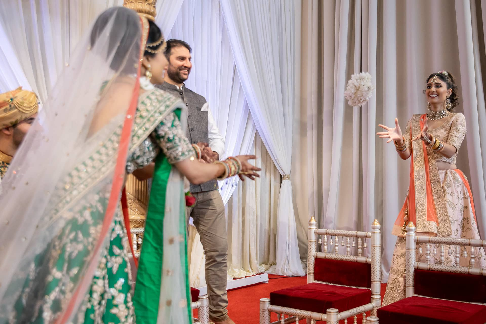Bride throwing flowers during Hindu wedding