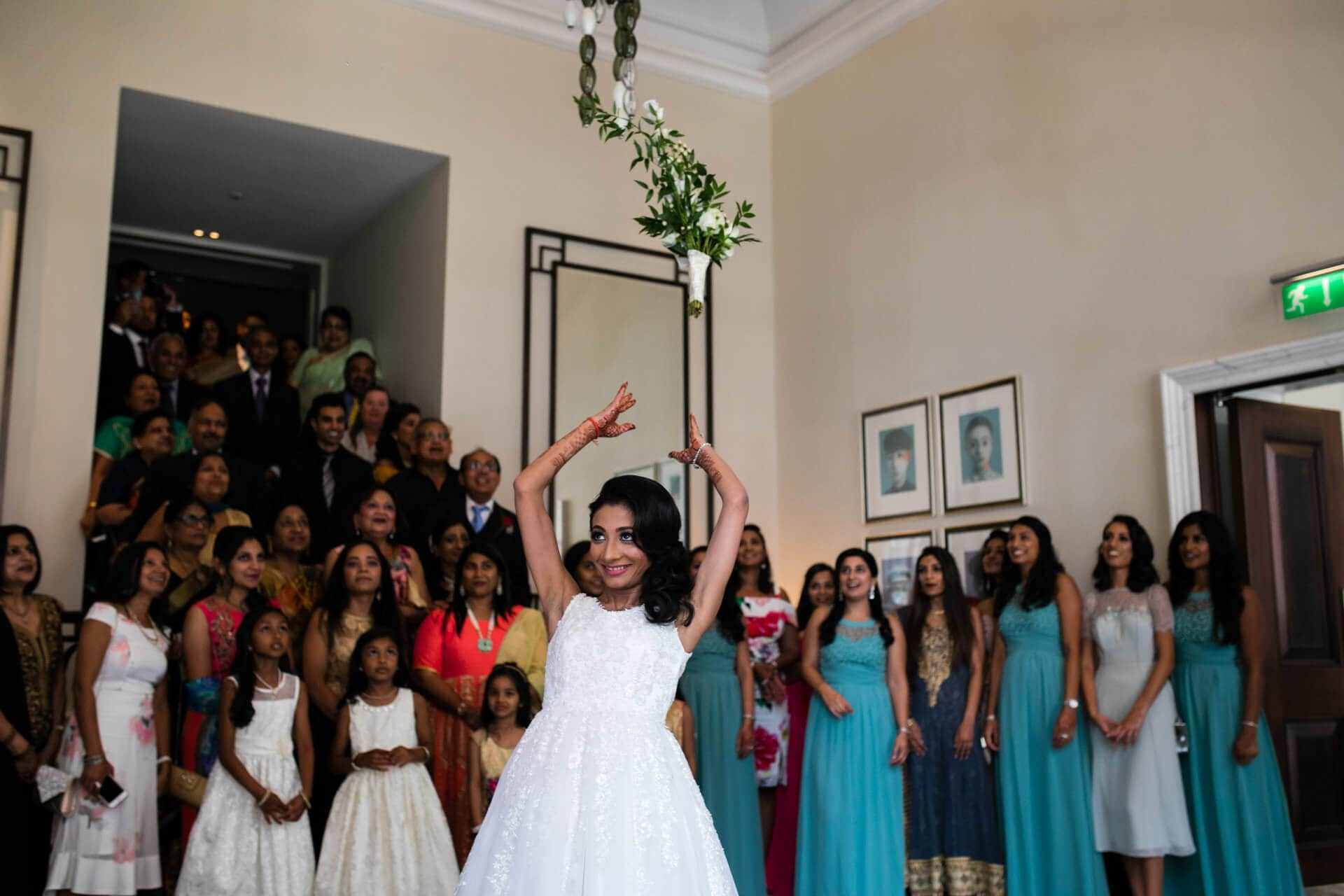 Bride throwing bouquet at Langham hotel wedding