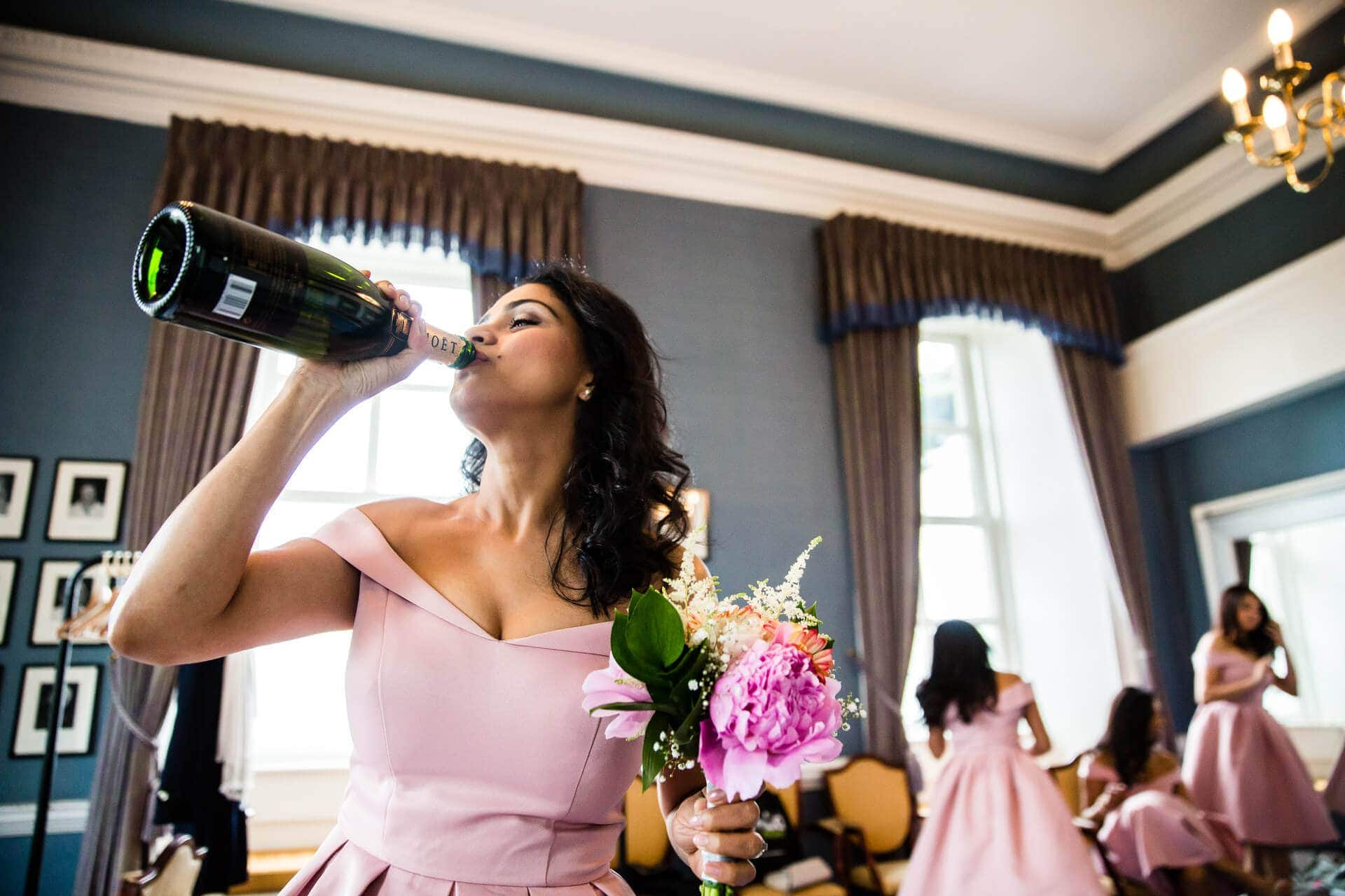 Bridesmaid drinking champagne from the bottle