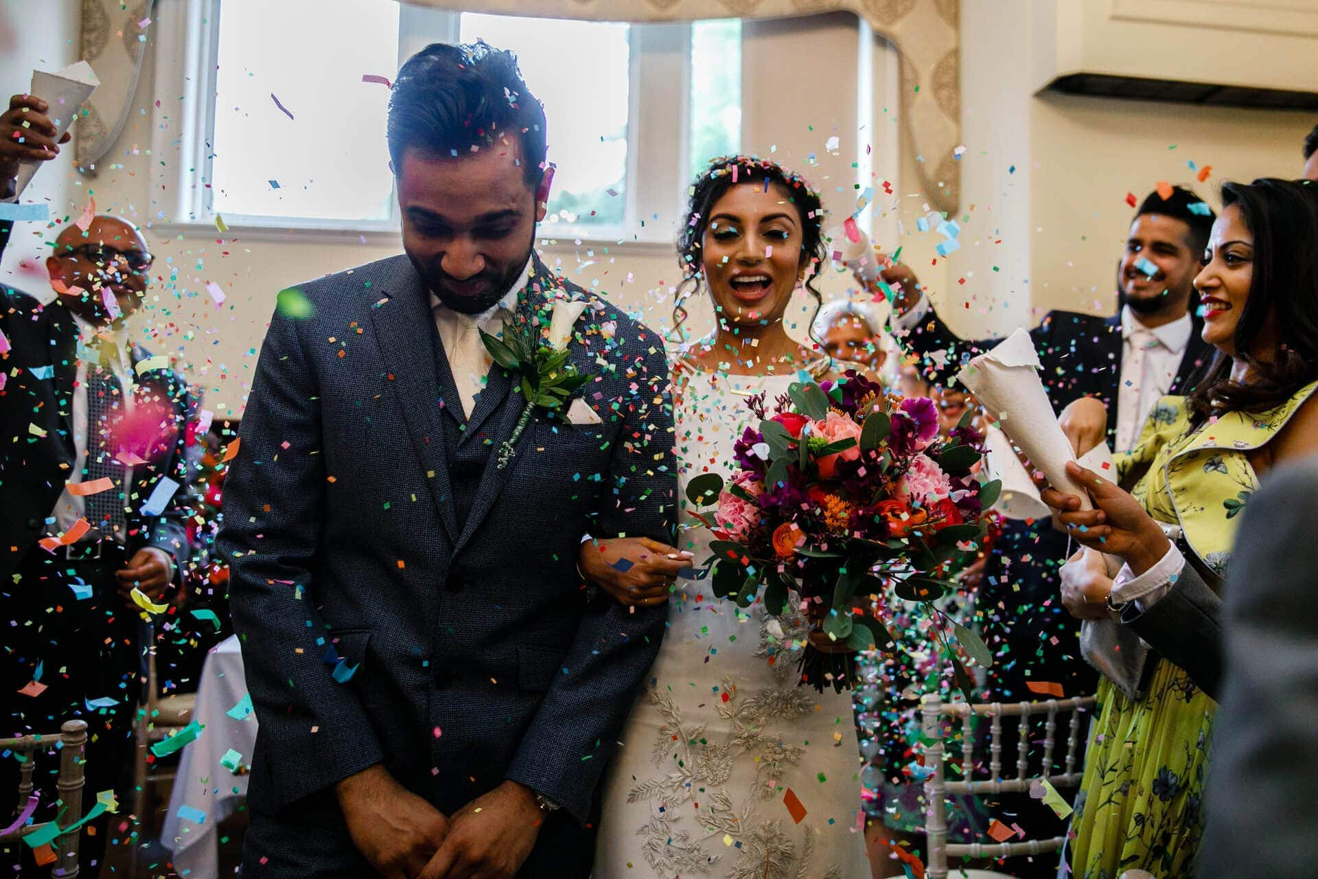 Bride and groom being showered with confetti