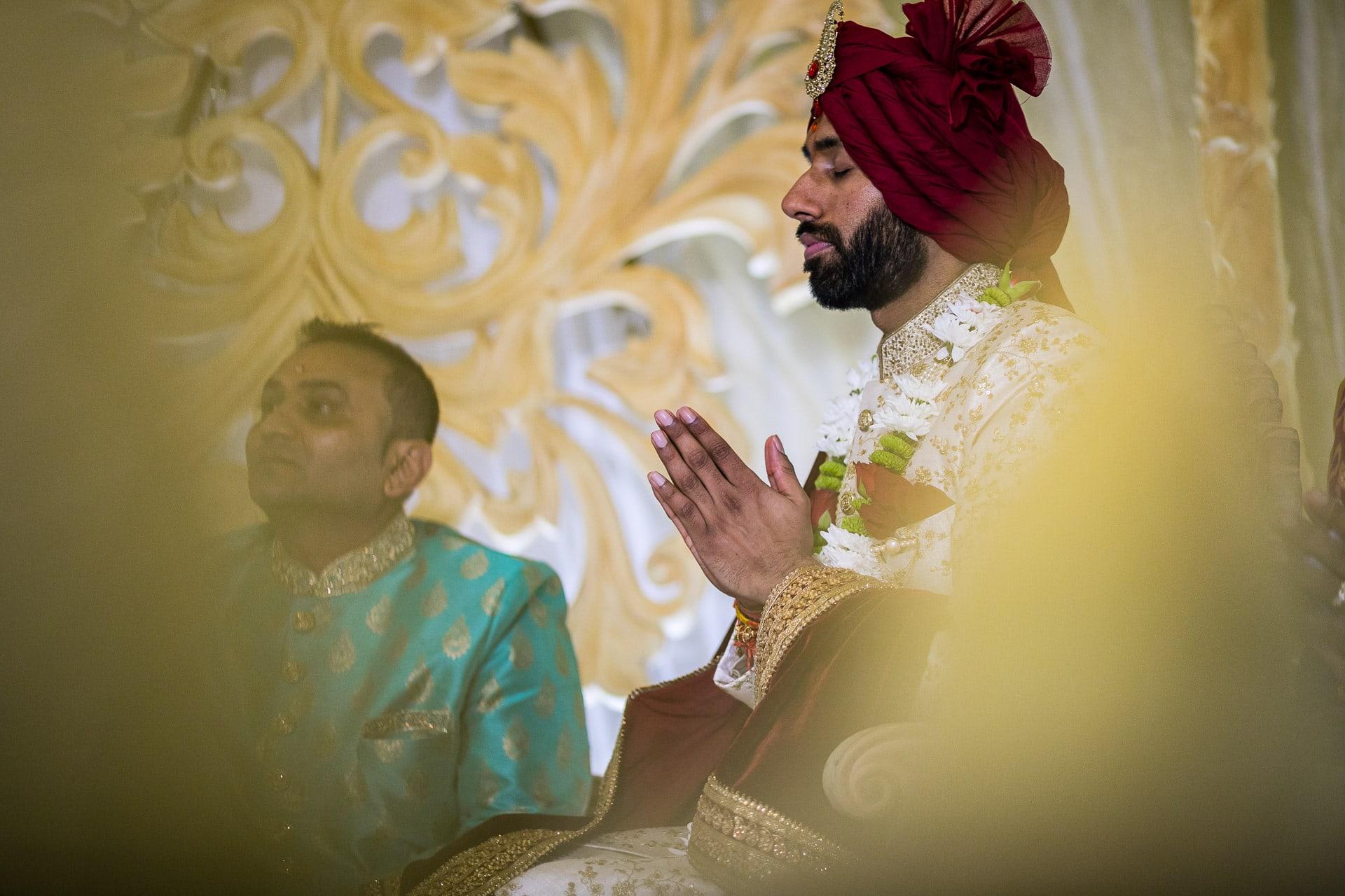 Asian wedding groom praying