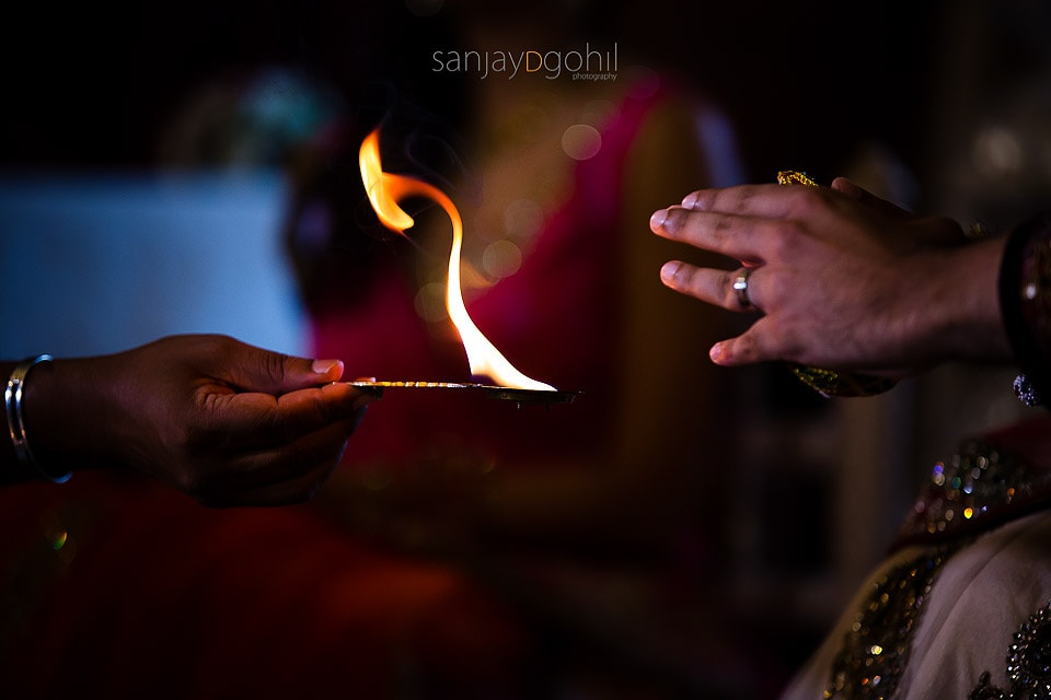 Closeup of hands and flame during Hindu Wedding ceremony