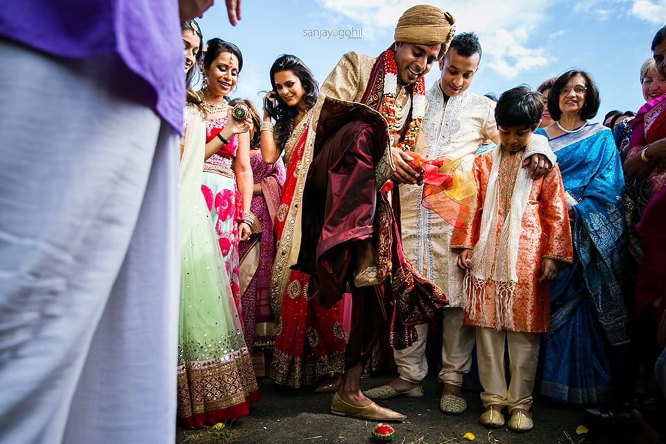 Groom crushing clay pot during wedding ceremony