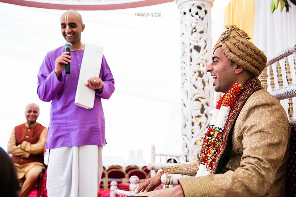 Groom in the mandap laughing with the priest