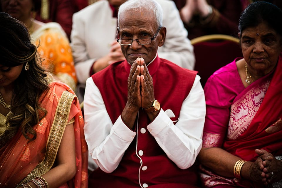 Asian Wedding guest praying