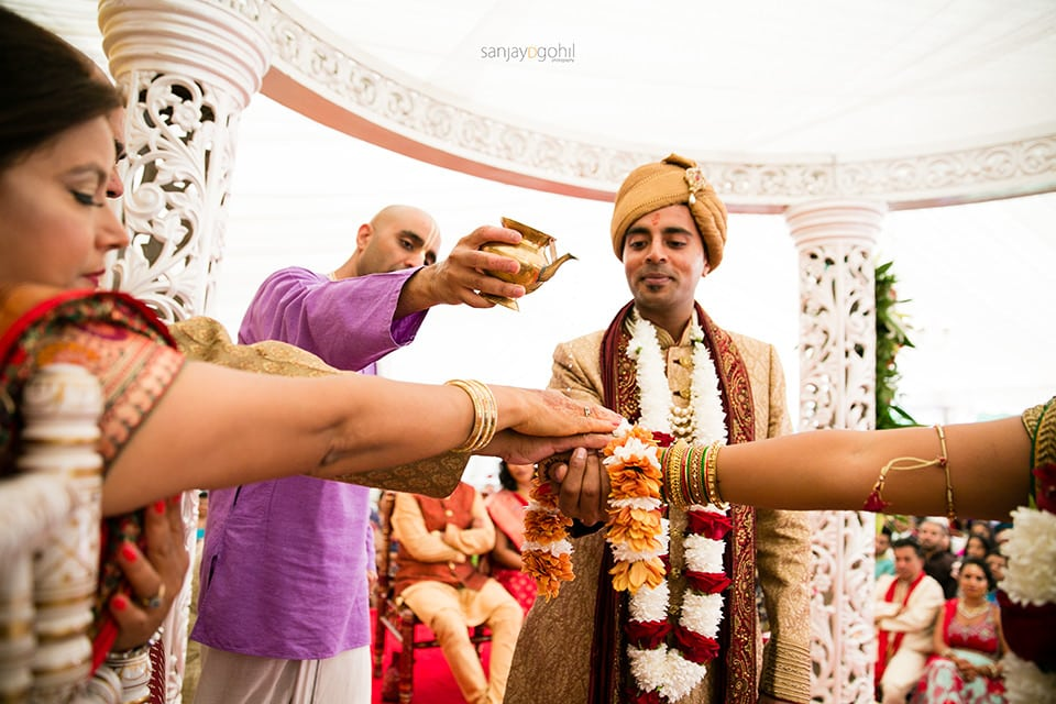 Water being poured to the hands of the bride and groom