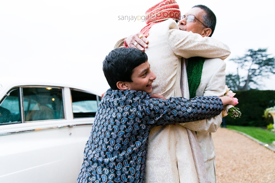 Groom hugging bride's father and cousin
