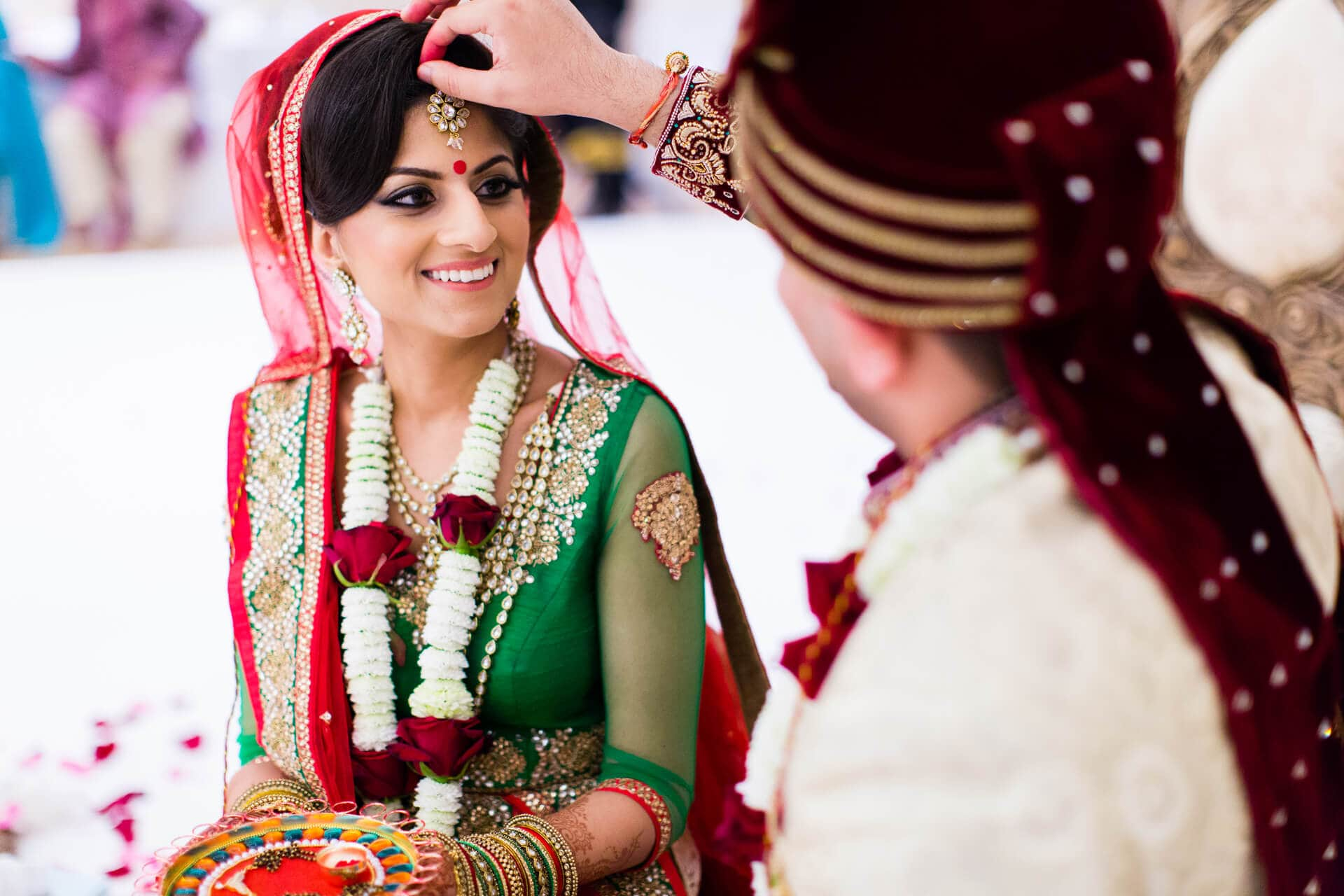 Groom placing sindoor onto bride