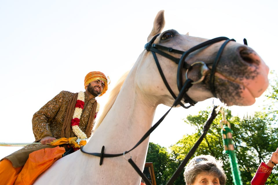 Asian Groom arriving at Savill Court on a white horse