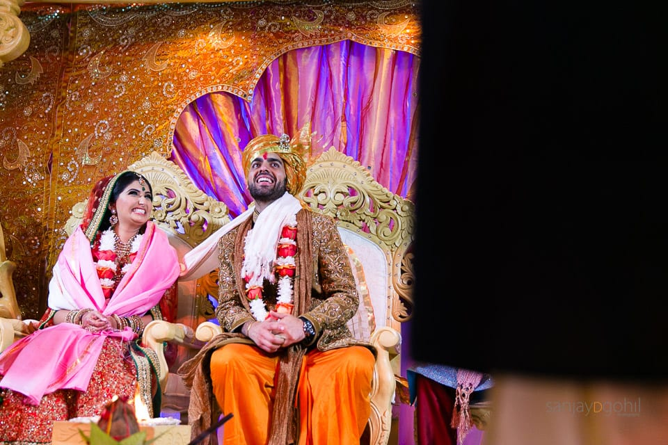 Asian Wedding bride and groom laughing in the mandap