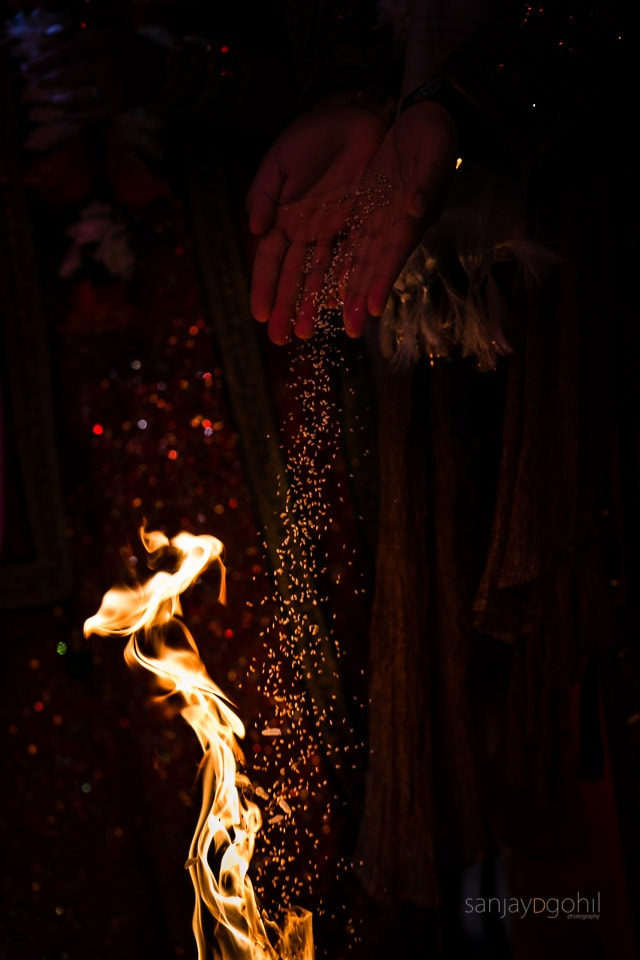 Seeds being poured into the fire during asian wedding ceremony