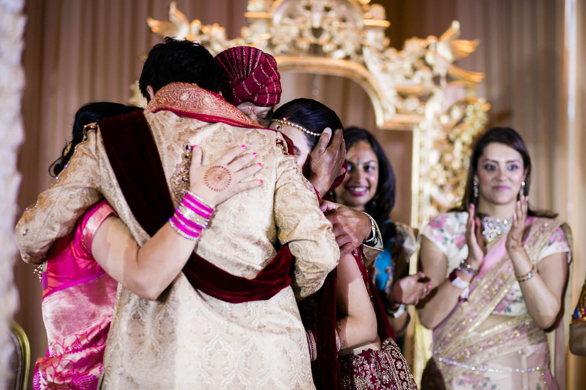 Family hugging after wedding ceremony