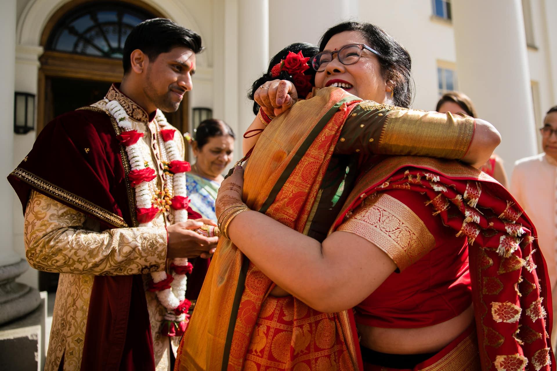 Mothers of wedding couple hugging