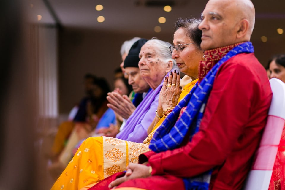 Asian wedding guests praying