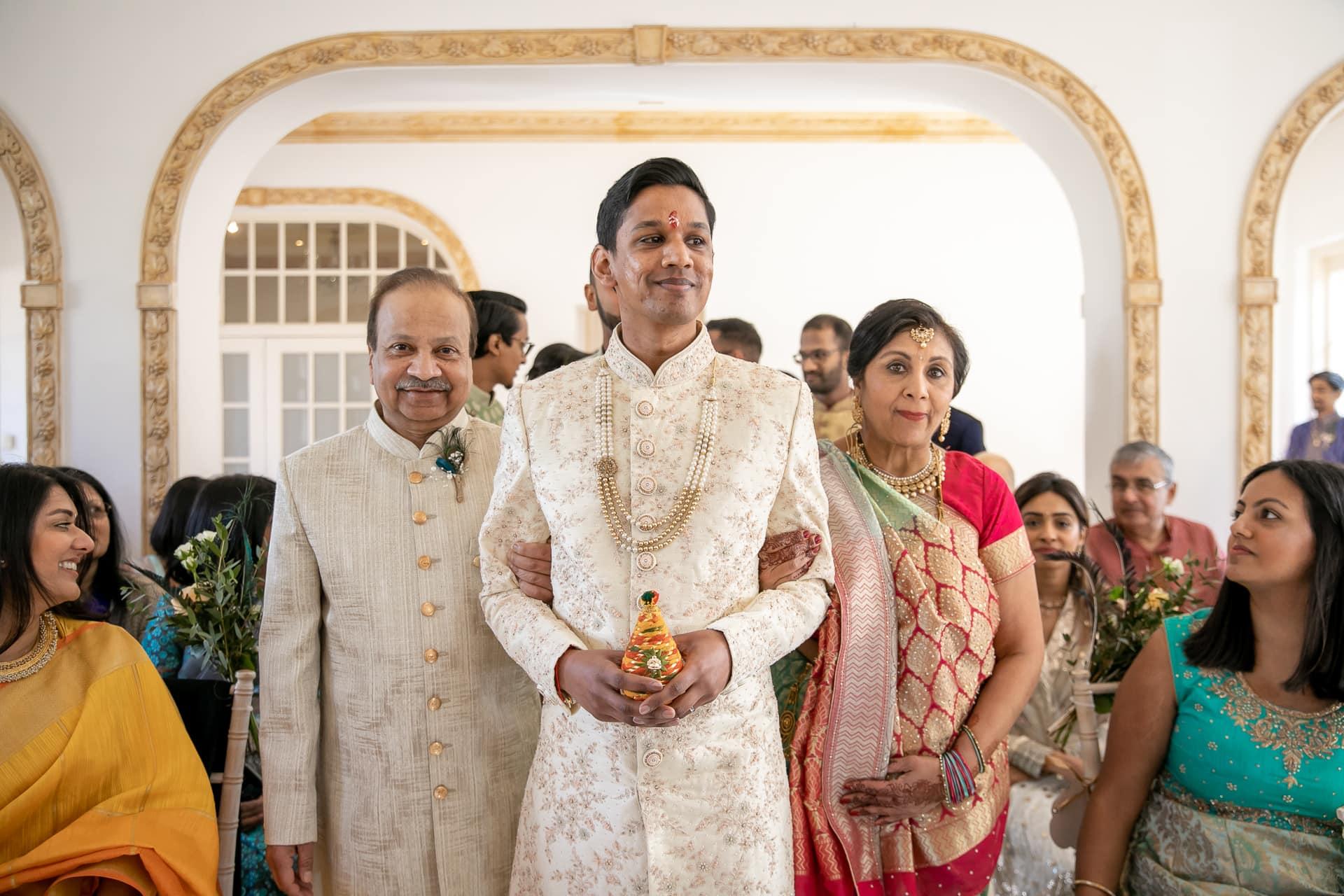 Hindu groom walking down the isle with bride's parents