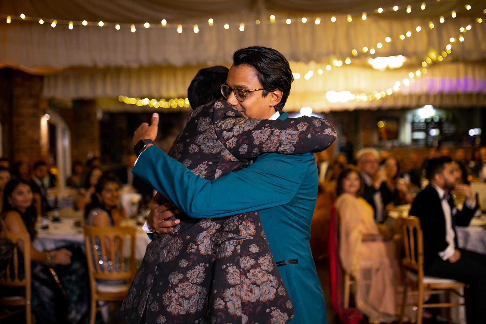 Groom hugging brother