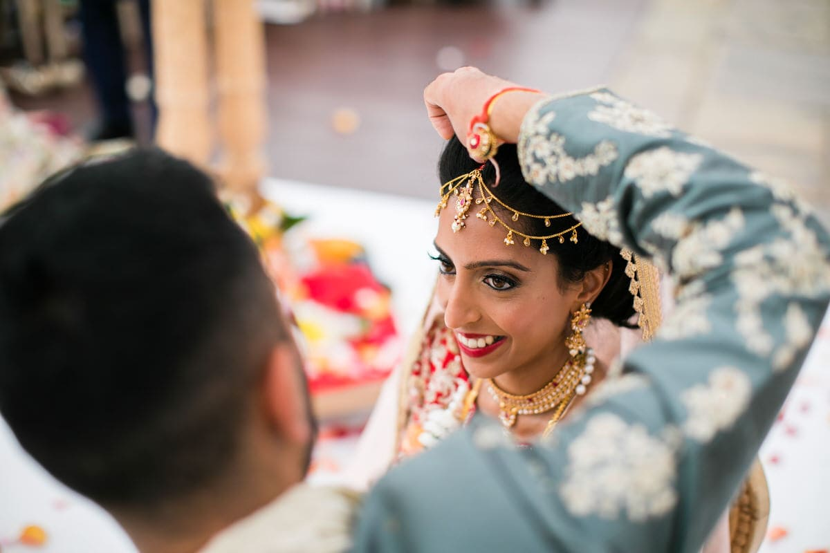 Groom placing sindoor into the parting of the bride's hair