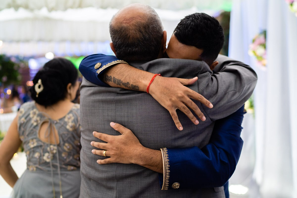 Groom hugging parents