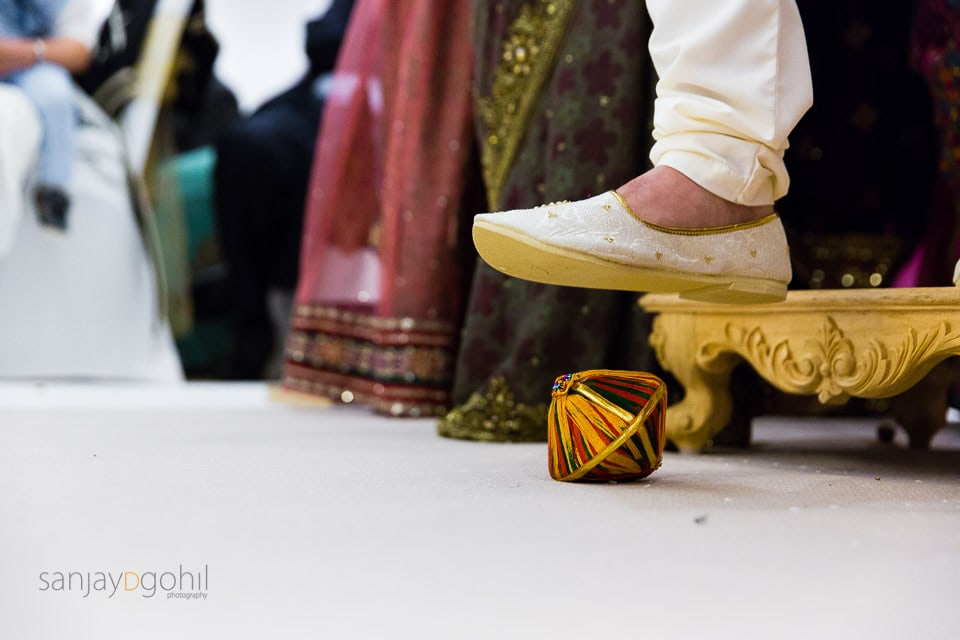 Groom stepping on clay pot during Hindu Wedding ceremony