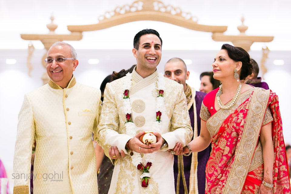 Groom walking and smiling with bride's parents