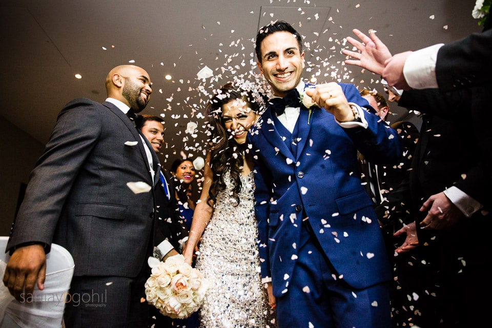 Confetti being poured onto bride and groom