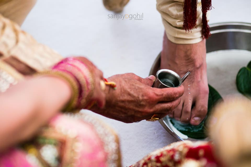 Water being poured onto the feet of the bride and groom