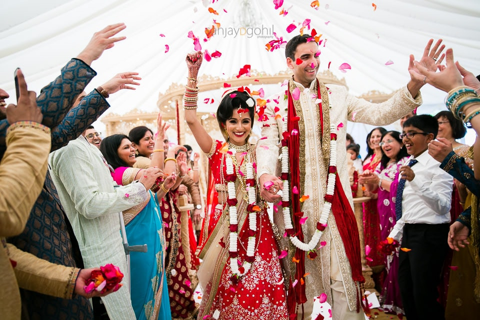 Bride and groom running down the isle while being showered with petals