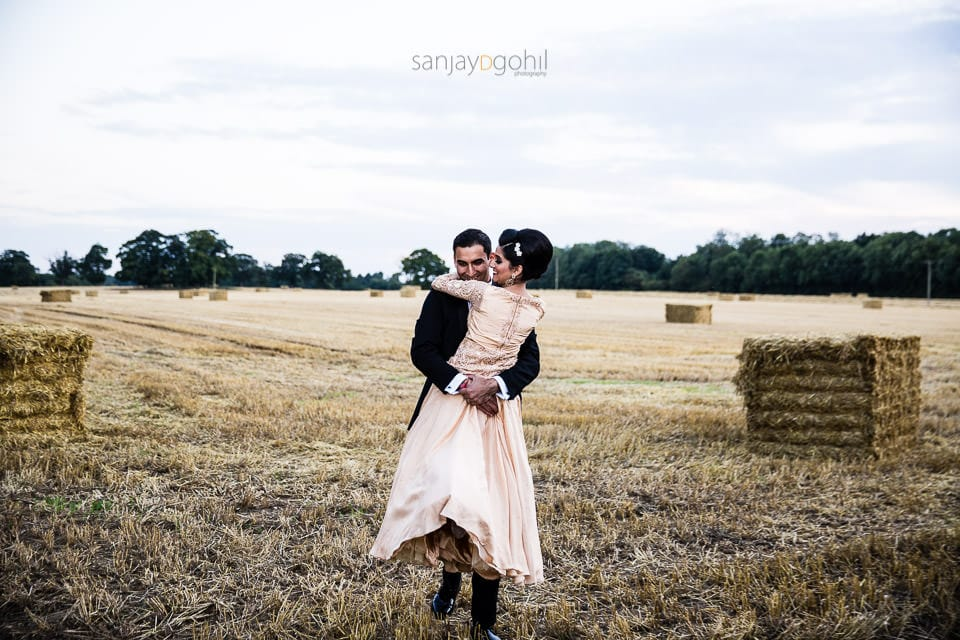 Groom carrying bride in the field