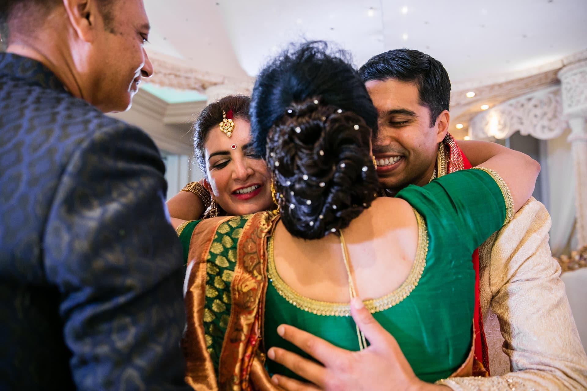 Wedding couple hugging parents