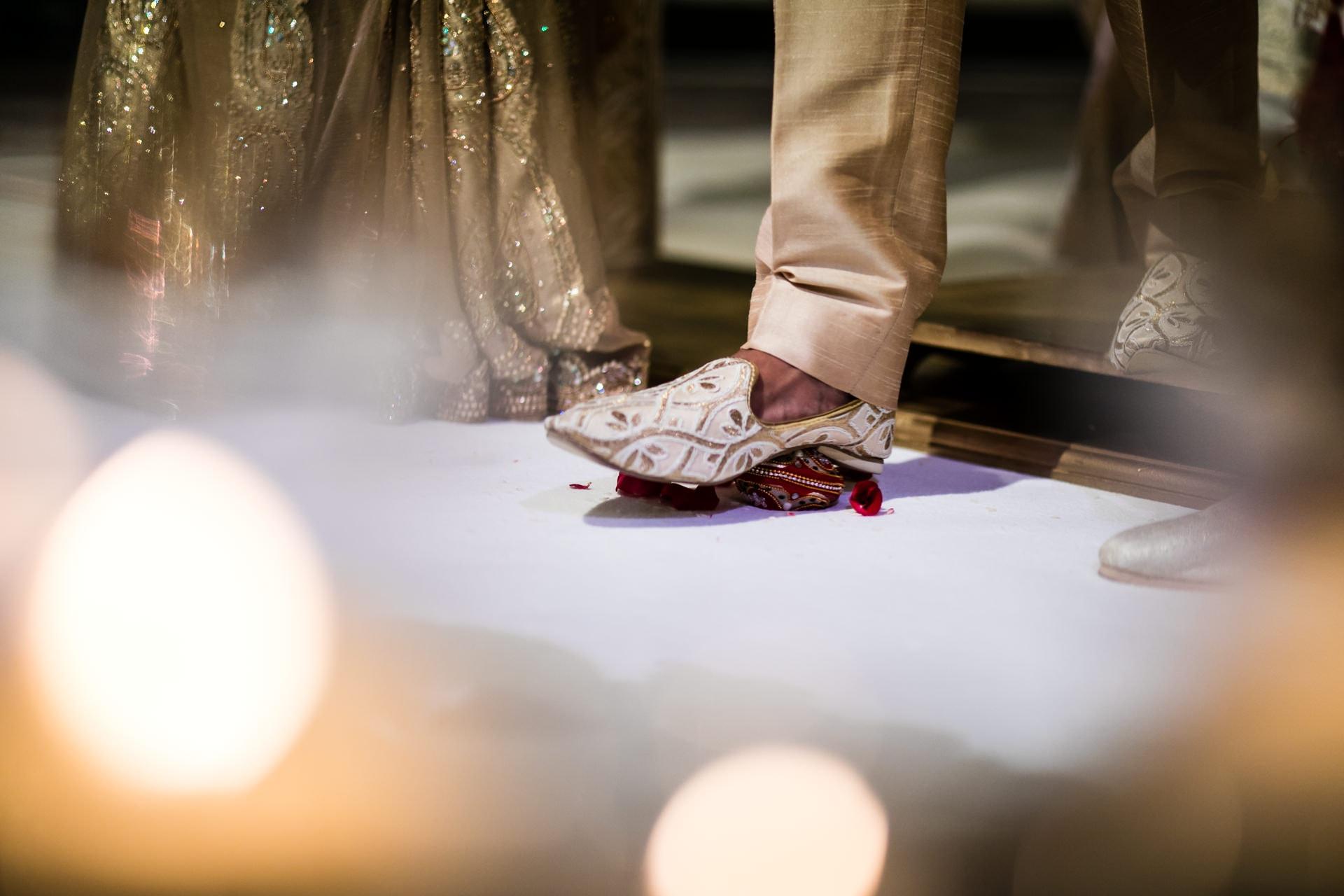 Hindu Wedding groom stepping on clay pot