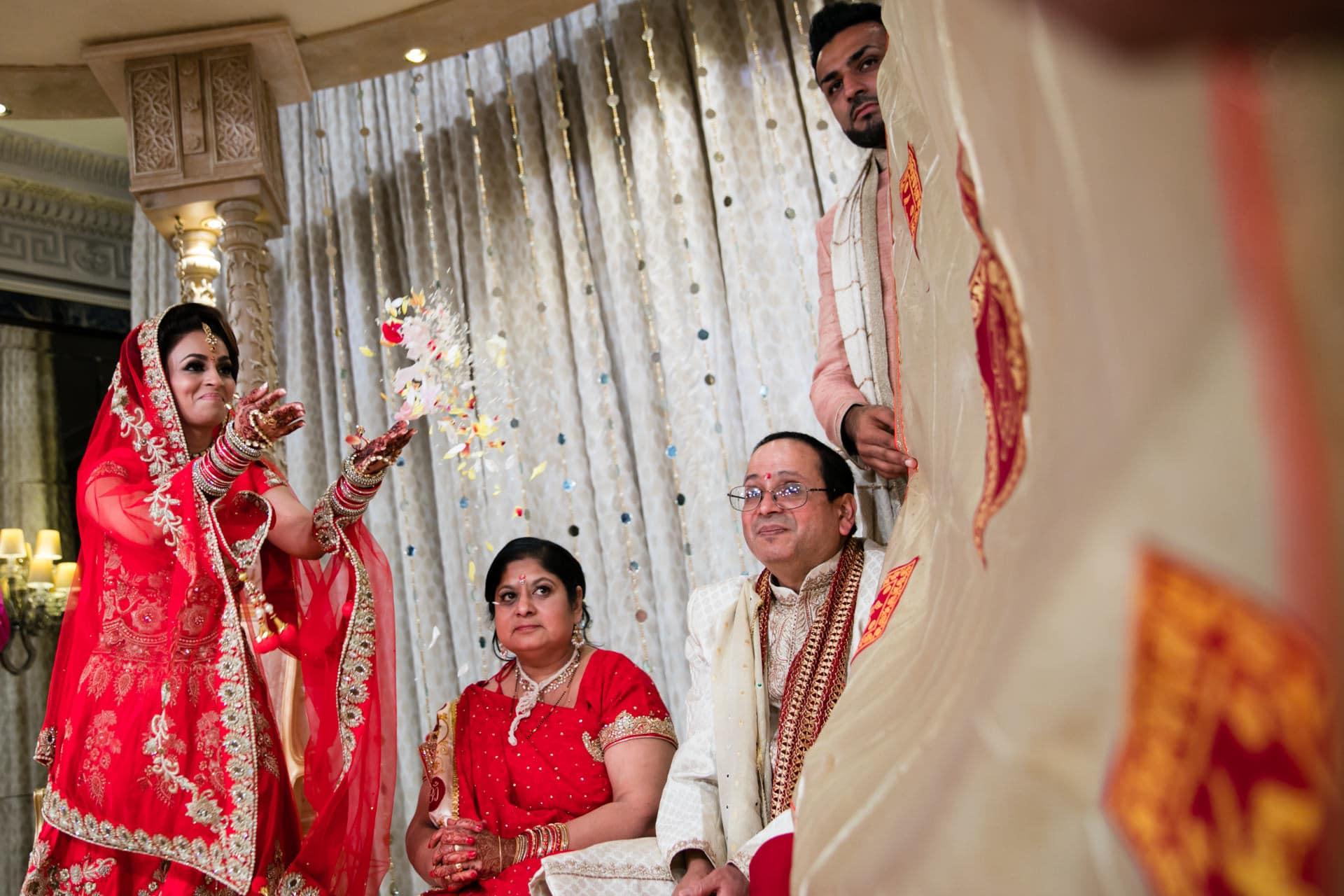 Bride throwing flowers towards the groom