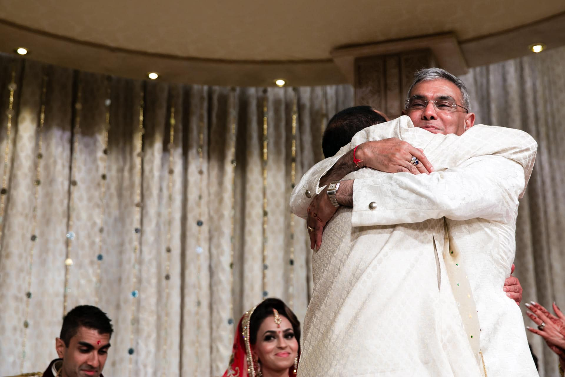 Fathers of bride and groom hugging