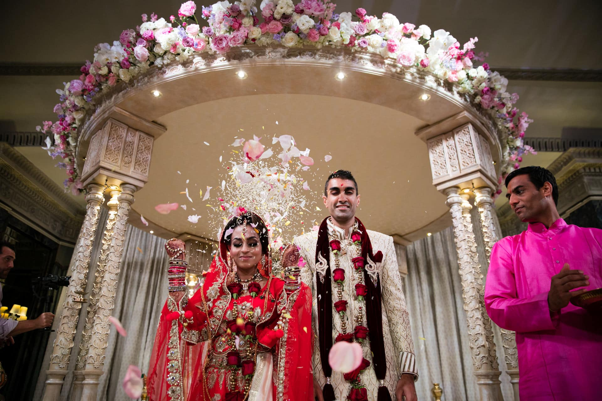 Bride throwing rice and flowers to close the Mandap