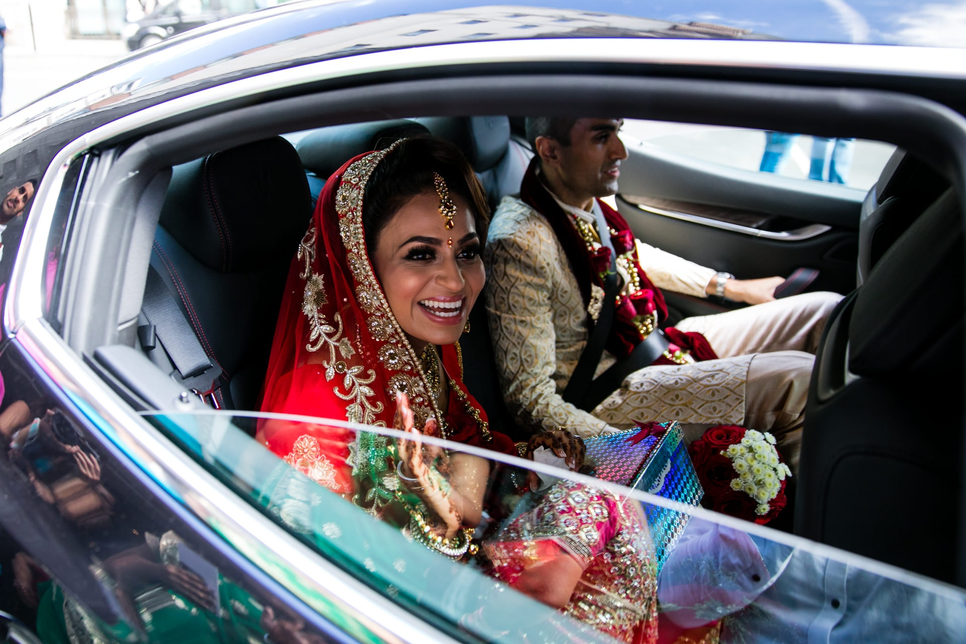 Asian Bride waving goodbye before the car leaves