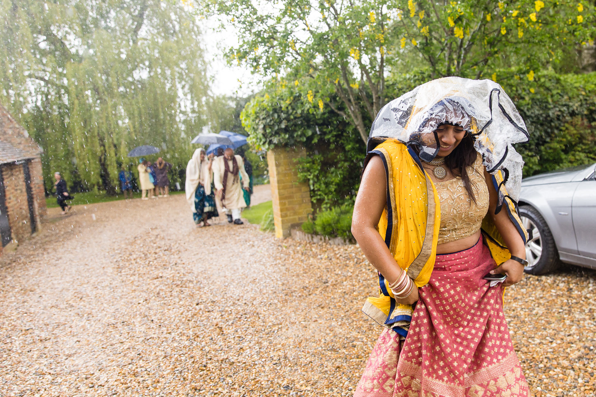 Asian wedding guests arriving for wedding in the rain