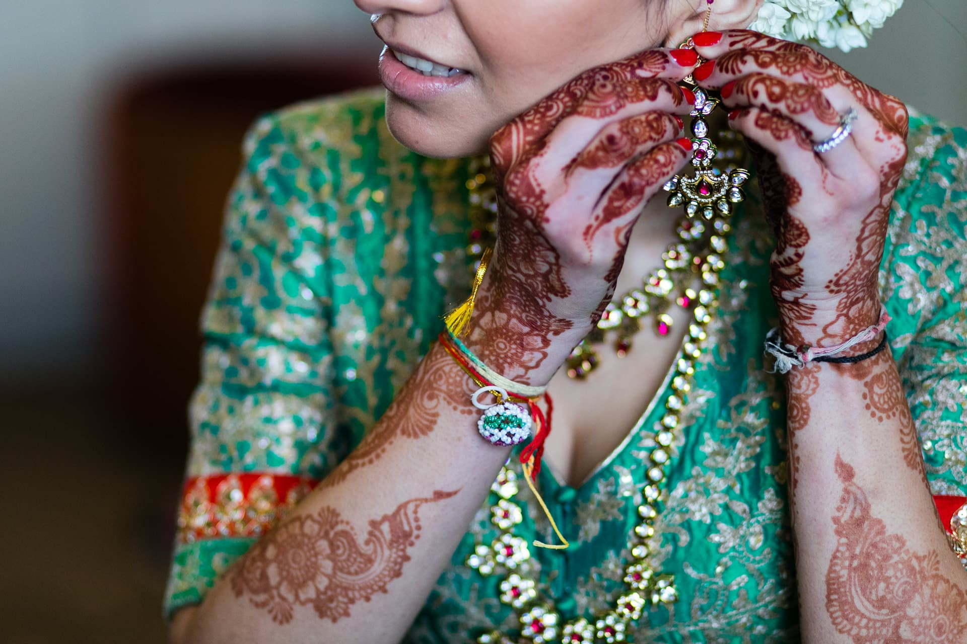 Asian bride putting earrings on