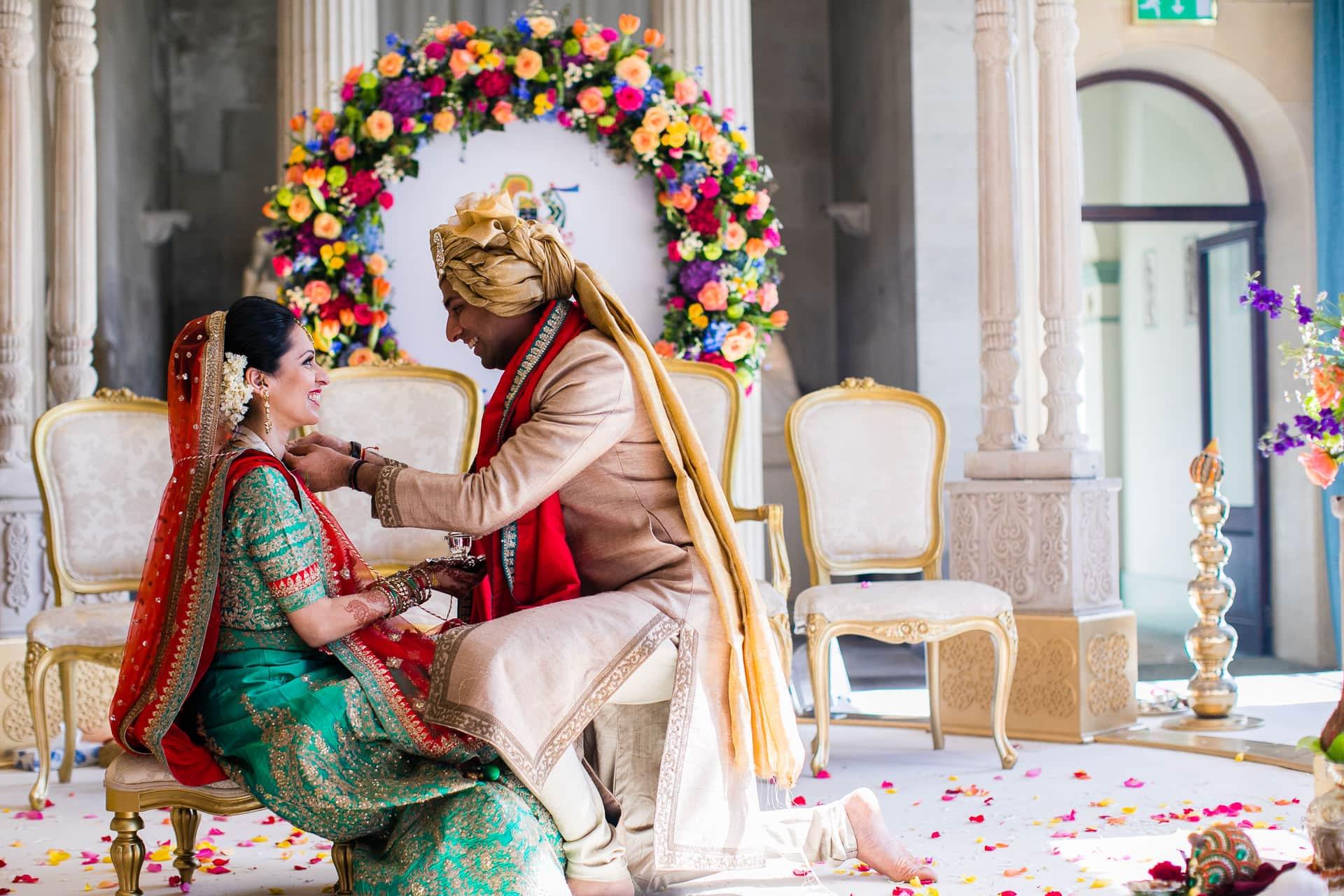 Groom putting Mangal Sutra onto bride