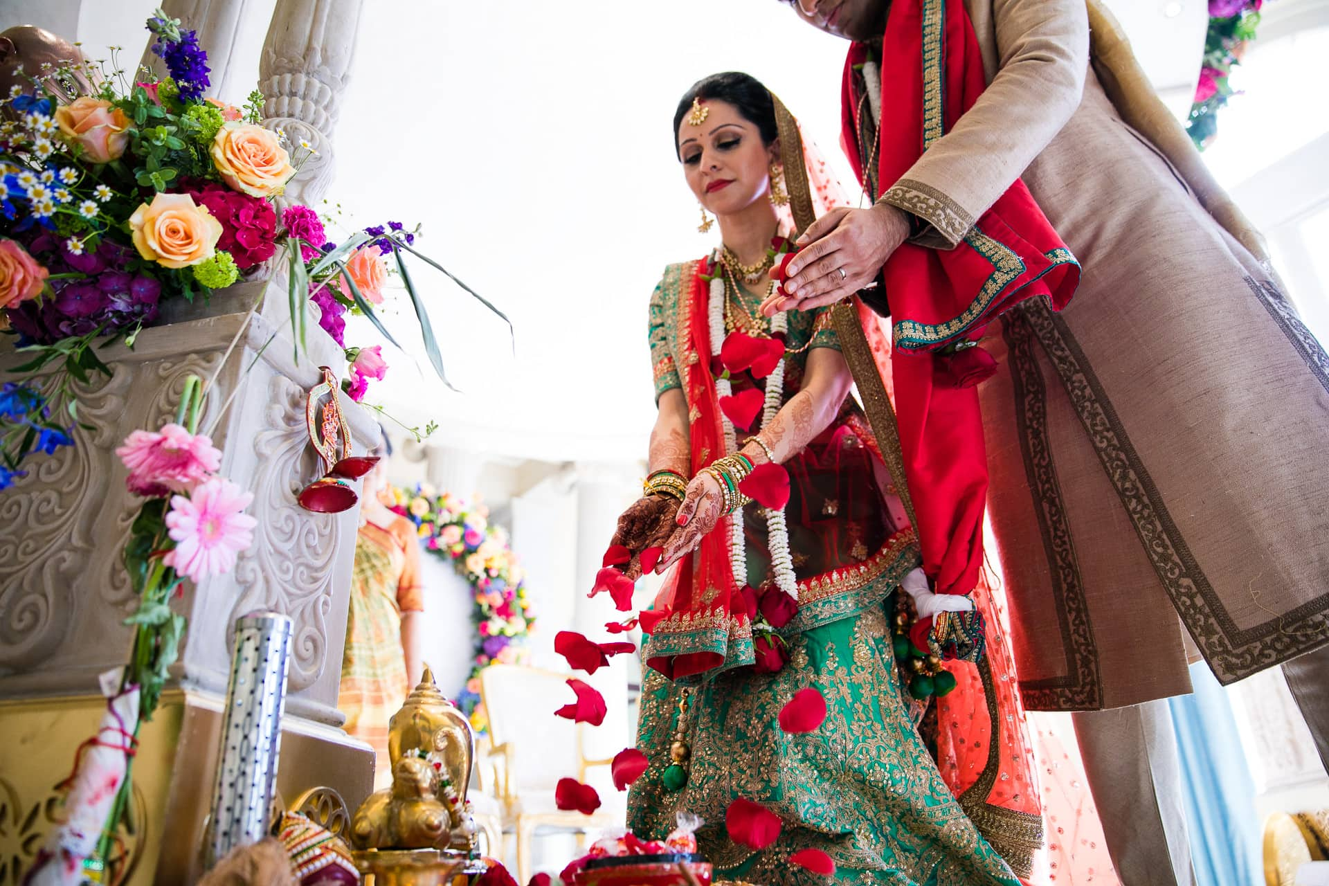 Wedding couple offering rose petals to Ganeshji