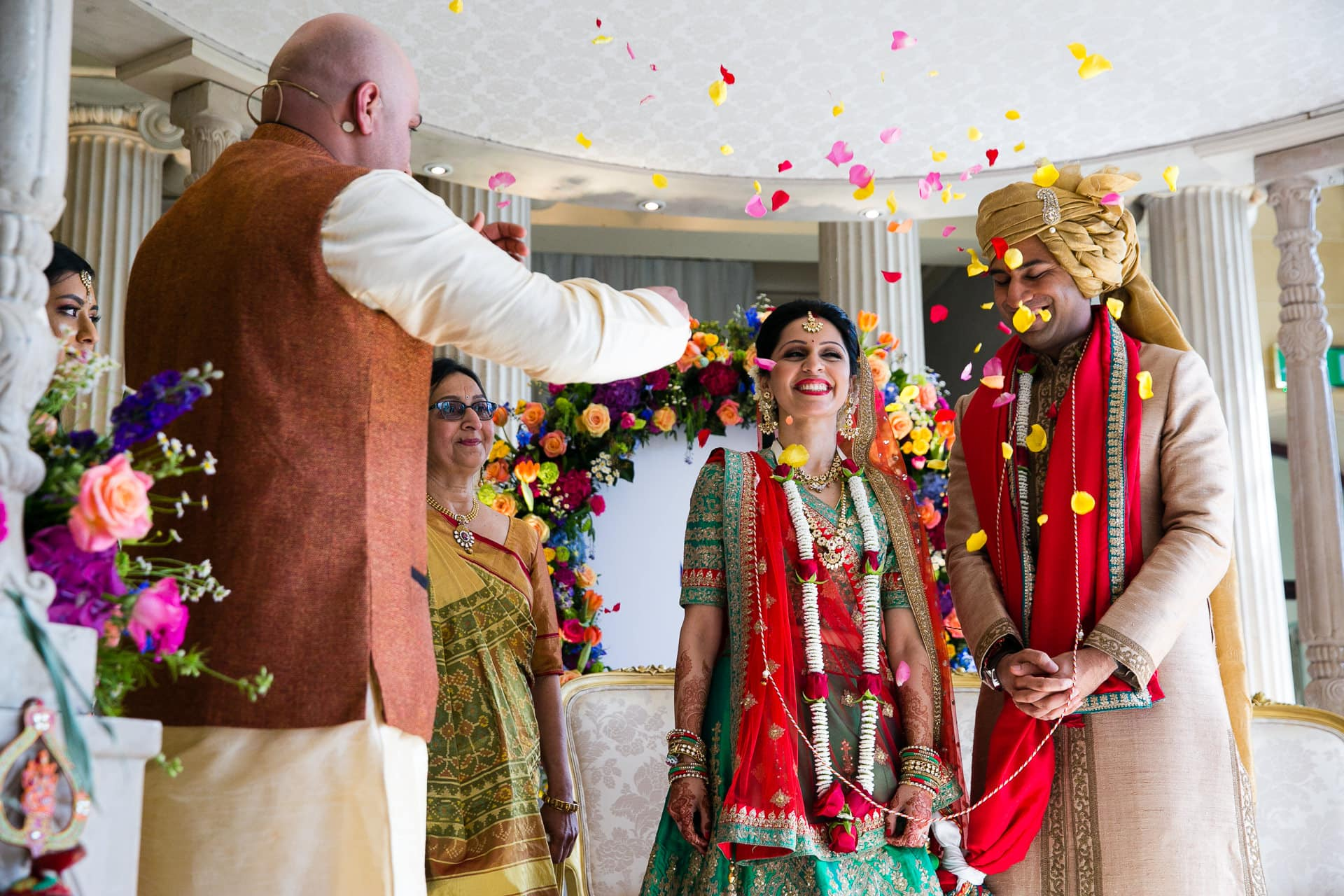 Bride and groom being showered with flowers by Pandit Paarth Joshi
