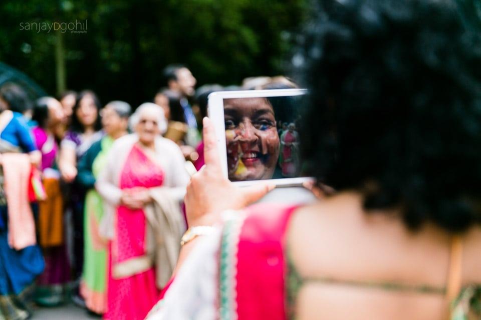 Hindu Wedding guest taking a photograph on iPad