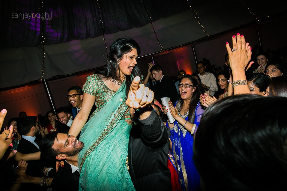 Asian wedding guests dancing during reception party at Saville Court