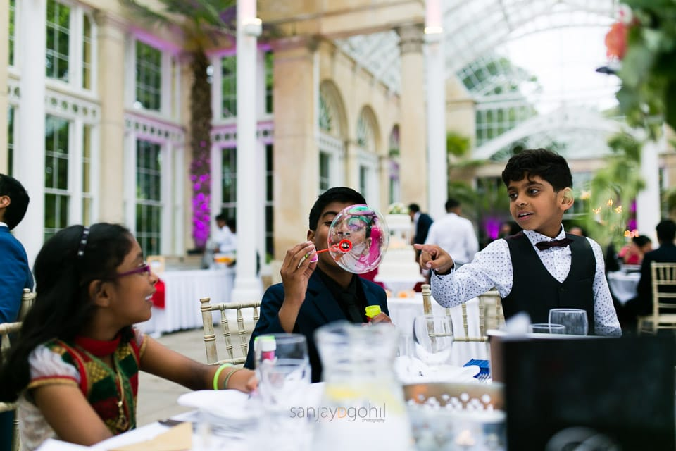Children blowing bubbles during reception party