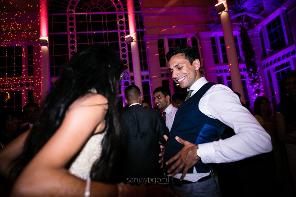 Asian Wedding guests dancing during reception party at Syon Conservatory