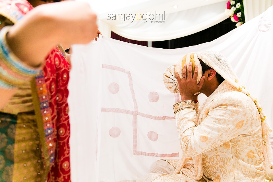 Asian Wedding groom covering his face