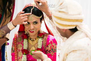 Sindoor being placed on forehead of the asian bride
