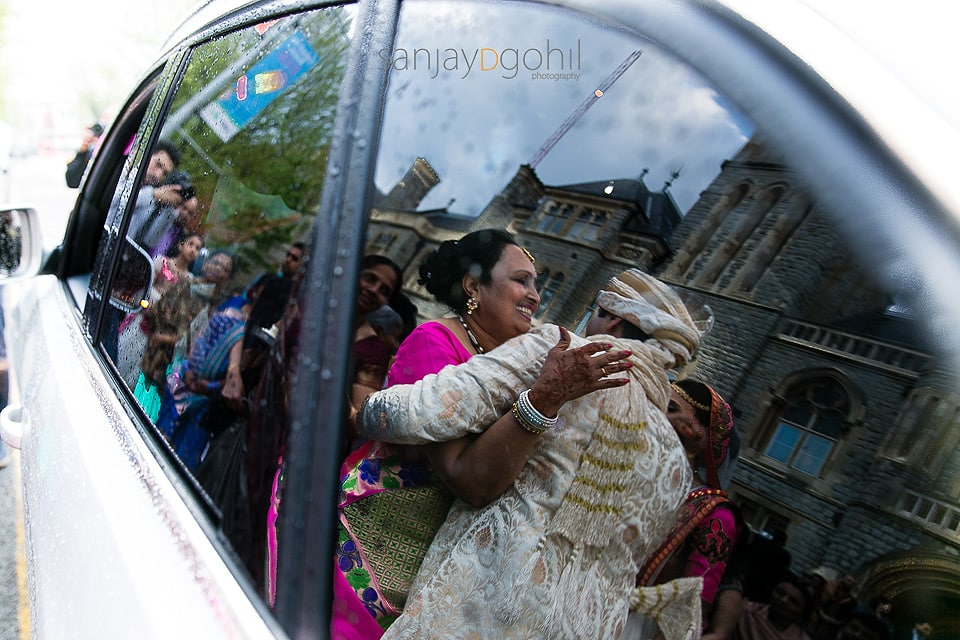 Reflection of bride's mum hugging groom