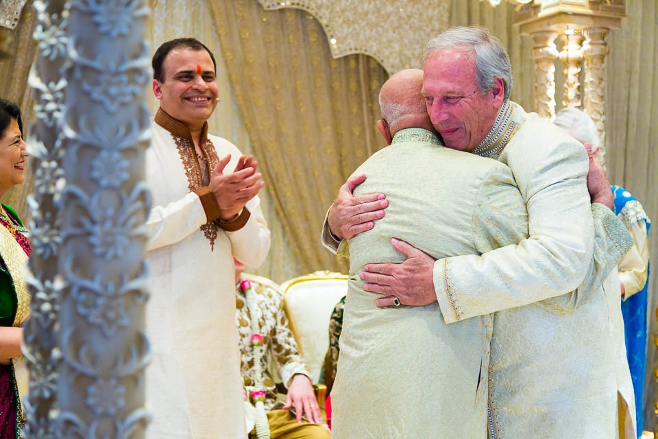 Fathers of the bride and groom hugging
