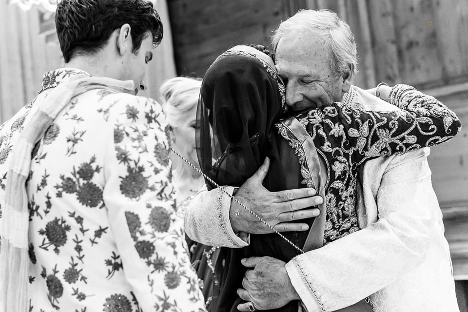 Father of groom hugging bride